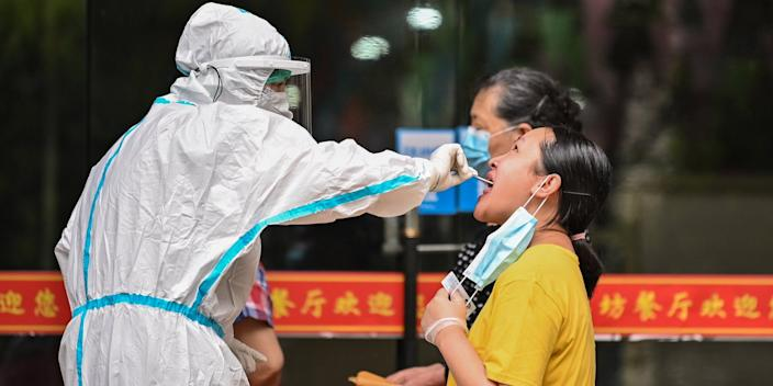 """A medical worker takes a swab sample from a man to be tested for the COVID-19 coronavirus next to a street in Wuhan, in Chinas central Hubei province on May 16, 2020. <p class=""""copyright"""">HECTOR RETAMAL/AFP via Getty Images</p>"""