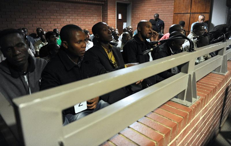 (FILES) A file picture taken on March 8, 2013 shows some of the nine South African policemen accused of the death of Mido Macia, a Mozambican taxi driver who died in custody after being dragged behind a South African police van, in Benoni court. One of the South African policemen on trial for the death of a Mozambican man who died after being dragged behind a moving police van testified on August 6, 2015 that he wanted to save him. Mido Macia, a taxi driver, was found dead in a police cell in February 2013 after he was handcuffed to the back of a police van and dragged hundreds of metres (yards) in Daveyton, east of Johannesburg. Eight officers are currently standing trial for his murder. AFP PHOTO / POOL / WERNER BEUKE (AFP Photo/Werner Beuke)