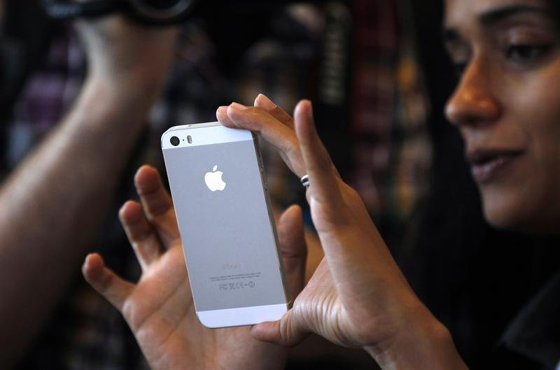 A woman tries the silver colored version of the new iPhone 5S after Apple Inc's media event in Cupertino