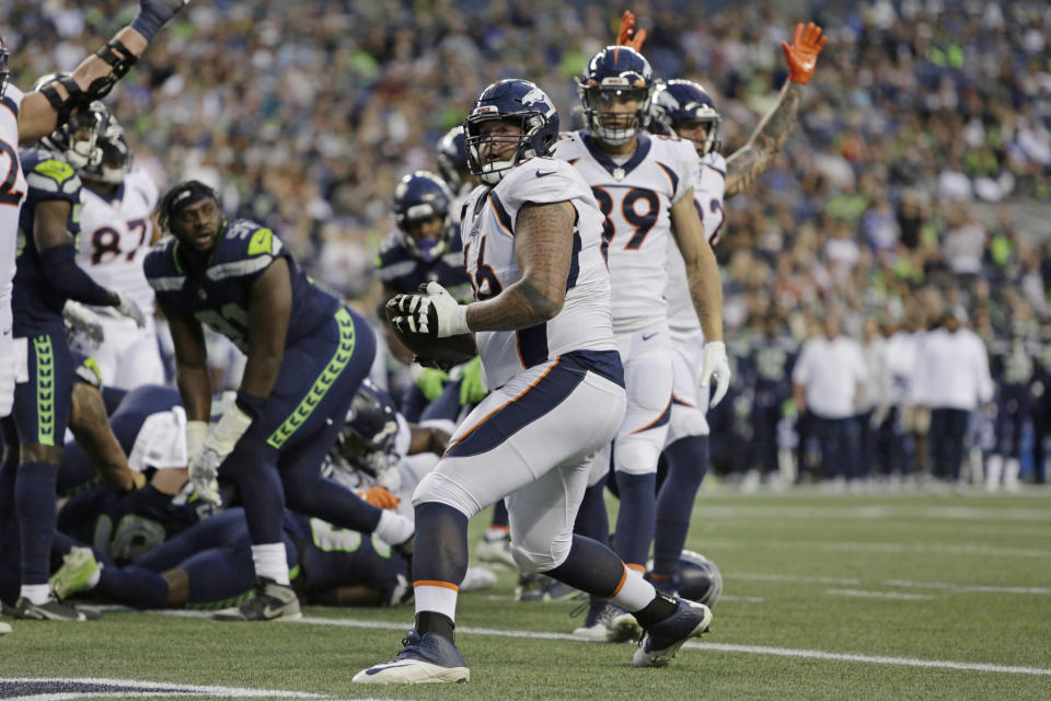 Denver Broncos offensive guard Dalton Risner holds the football after he recovered the ball after Broncos running back Javonte Williams scored a touchdown during the first half of an NFL preseason football game against the Seattle Seahawks, Saturday, Aug. 21, 2021, in Seattle. (AP Photo/Jason Redmond)