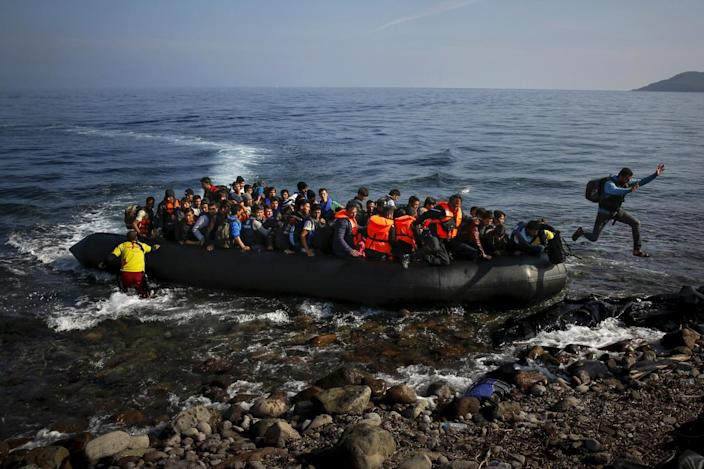 <p>An Afghan migrant jumps off an overcrowded raft onto a beach at the Greek island of Lesbos, Oct. 19, 2015.<i> (Yannis Behrakis/Reuters)</i></p>
