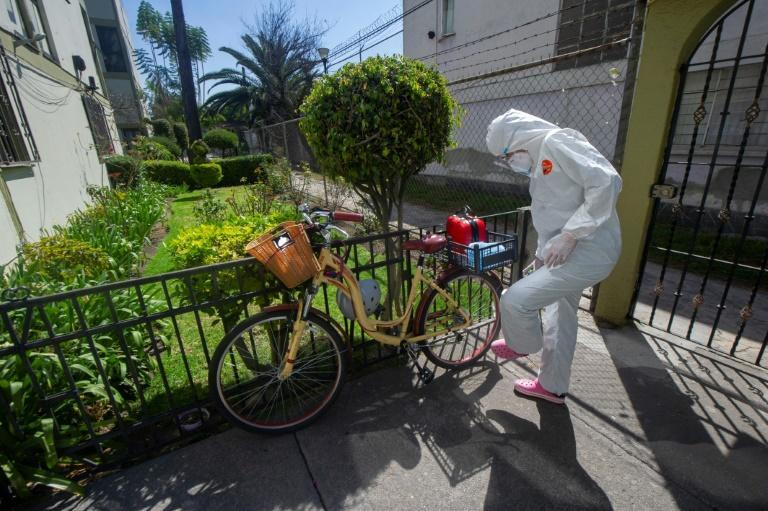 Mexican doctor Karla Montano disinfects her shoes before entering the home of a coronavirus patient