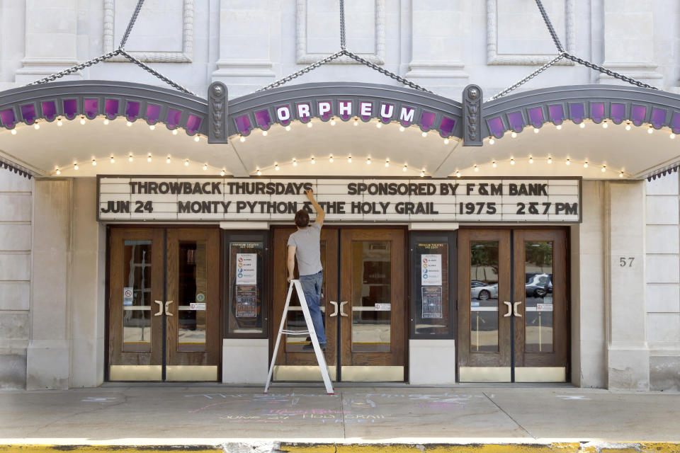 """Ross McIntire, technical director of the Orpheum Theatre, also known as the """"Jewel of Galesburg,"""" updates the marquee Thursday, June 17, 2021 in downtown Galesburg, Ill. Before 1969, Blacks and Hispanics were relegated to the balcony of the Orpheum. Decades before, Mexican immigrants and their families coming to work on the railroad were barred from the city and settled in tent camps outside of it. (AP Photo/Shafkat Anowar)"""