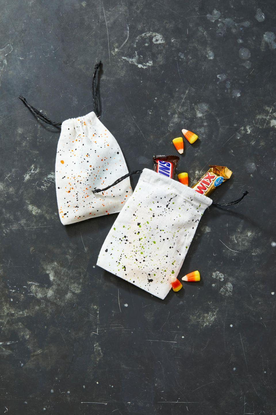 "<p>Use these treat bags to dole out candy to trick-or-treaters, or as Halloween party favors. To make them, just mix water with acrylic paint until it reaches the consistency of heavy cream. Coat a craft brush with paint and then lightly tap it repeatedly over a small muslin drawstring bag. You can also use an old toothbrush by dipping it into paint and then, using your finger, flick the bristles onto the bag. Let it dry completely and repeat on other side.</p><p><a class=""link rapid-noclick-resp"" href=""https://www.amazon.com/Percent-Cotton-Muslin-Drawstring-12-Pack/dp/B01H9YKCKW?tag=syn-yahoo-20&ascsubtag=%5Bartid%7C10055.g.22062770%5Bsrc%7Cyahoo-us"" rel=""nofollow noopener"" target=""_blank"" data-ylk=""slk:SHOP MUSLIN BAGS"">SHOP MUSLIN BAGS </a></p>"