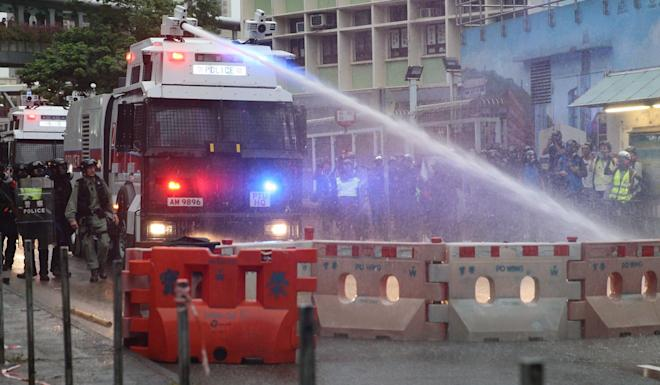 Police use a water cannon vehicle to clear the road in Tsuen Wan. Photo: EPA-EFE