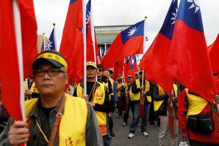 Protesters hold Taiwanese national flags as they take part in a rally against the overhaul of the military and civil service pension fund, outside the Presidential Office in Taipei,Taiwan January 22, 2017. REUTERS/Tyrone Siu