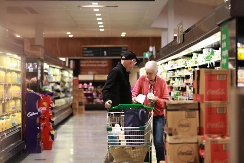 Pictured is an elderly couple shopping in a Woolworths supermarket aisle.