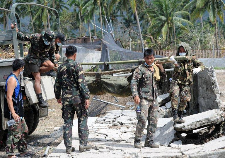 Soldiers unload a body bag containing a victim of Typhoon Bopha, in the southern Philippines, on December 8, 2012