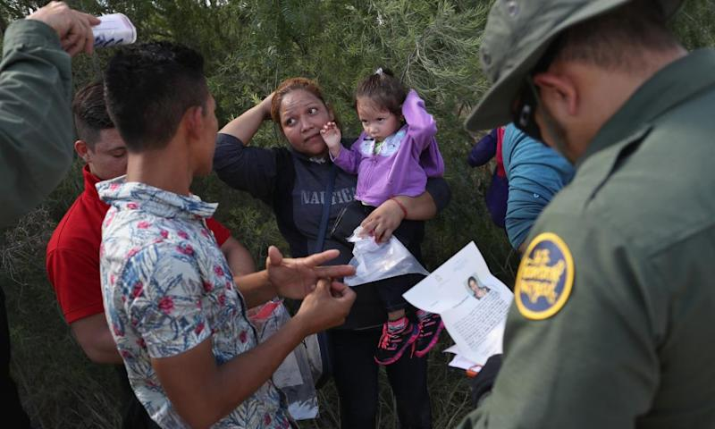Border patrol officers talk with a group of Central American asylum seekers before taking them into custody on 12 June 2018 near McAllen, Texas.