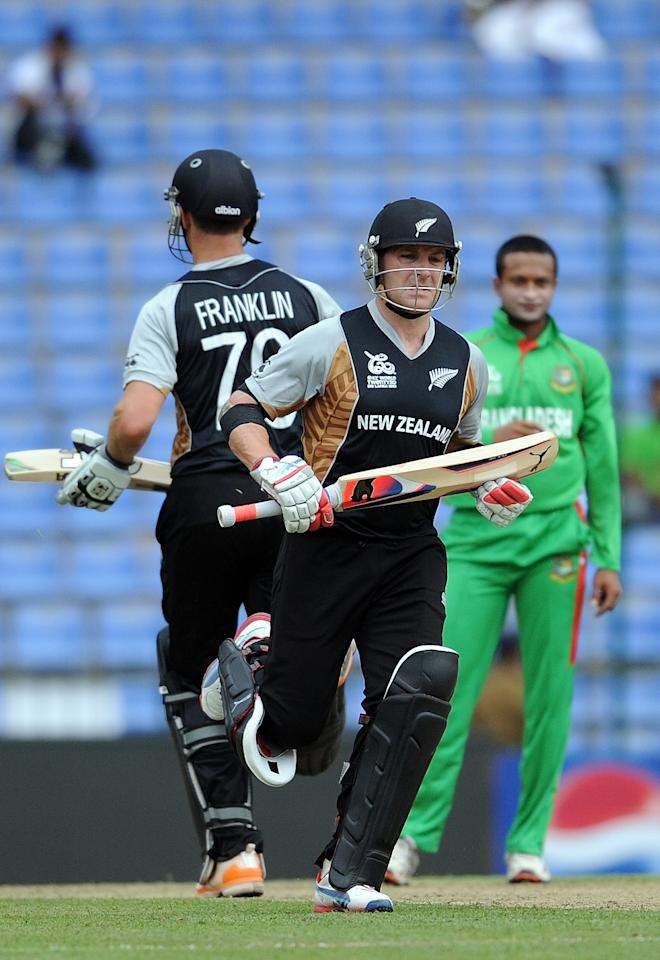 Bangladesh cricketer Shakib Al Hasan (R) watches as New Zealand batsman James Franklin (L) and Brendon McCullum (C) run between the wickets during The ICC Twenty20 Cricket World Cup match between Bangladesh and New Zealand at the Pallekele International Cricket Stadium in Pallekele  on September 21, 2012. AFP PHOTO/ Prakash SINGH