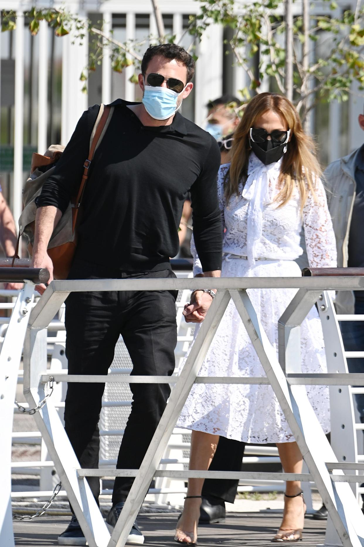 Ben Affleck, dressed in an all-black outfit, holds hands with Jennifer Lopez, wearing a Valentino lace shirt dress, as the pair arrive at the 78th Venice International Film Festival on September 09, 2021 in Venice, Italy. (Getty Images)