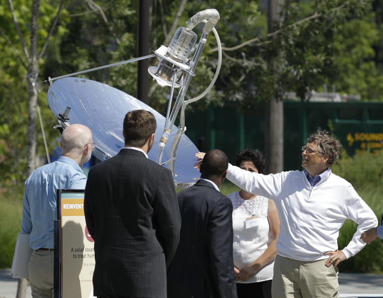 """Bill Gates, right, looks at a device that uses solar energy to treat human waste, as he tours the """"Reinventing the Toliet"""" Fair, Tuesday, Aug. 14, 2012, in Seattle, which is part of a Bill & Melinda Gates Foundation competition to reinvent the toilet for the 2.6 billion people around the world who don't have access to modern sanitation. (AP Photo/Ted S. Warren)"""