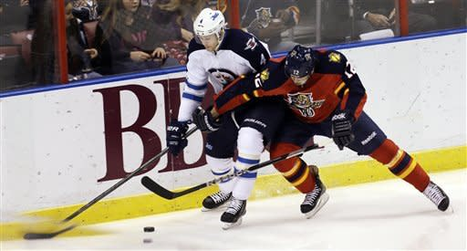 Winnipeg Jets' Paul Postma (4) and Florida Panthers' Jack Skille (12) battle for the puck during the first period of an NHL hockey game in Sunrise, Fla., Tuesday, March 5, 2013. (AP Photo/J Pat Carter)