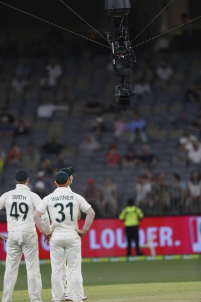 Australian players look at a cable suspended Television camera that got stuck over the pitch, holding up play during their cricket test against New Zealand in Perth, Australia, Sunday, Dec. 15, 2019. (AP Photo/Trevor Collens)