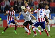 Valencia's midfielder Javi Fuego (C) controls a ball next to Atletico Madrid's midfielder Tiago (R) at the Vicente Calderon stadium in Madrid on March 8, 2015 (AFP Photo/Gerard Julien)