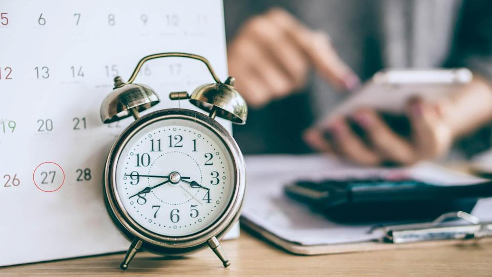due date calendar and alarm clock with blur business woman hand calculating  monthly expenses during tax season.
