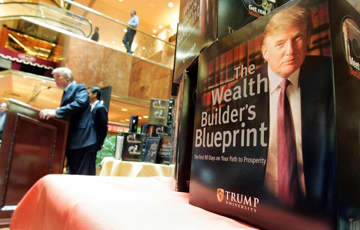 Course material is displayed while Donald Trump speaks at a news conference announcing the establishment of Trump University in 2005. (Photo: Mario Tama/Getty Images)
