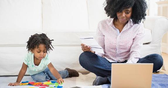 Mom browsing laptop, sitting on the floor with playing toddler copyright JGI/Jamie Grill/Shutterstock.com