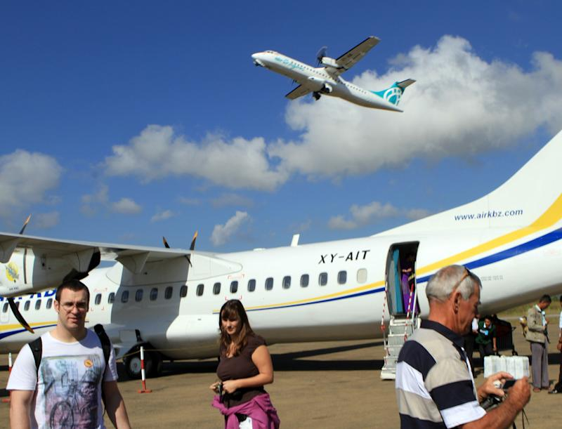 In this photo taken Nov. 9, 2011, an Air Bagan plane takes off as tourists arrive at Heho airport in Heho, Shan State, Myanmar. The Myanmar's domestic airline's Fokker-100, not the same type of plane shown in the photo, made an emergency landing in central Myanmar Tuesday, Dec. 25, 2012, on a road, killing two people and injuring 11, officials said.  The Air Bagan flight was carrying 65 passengers from Yangon, Myanmar's largest city, to Heho, the gateway to a popular tourist destination, Inle Lake.   (AP Photo/Khin Maung Win)