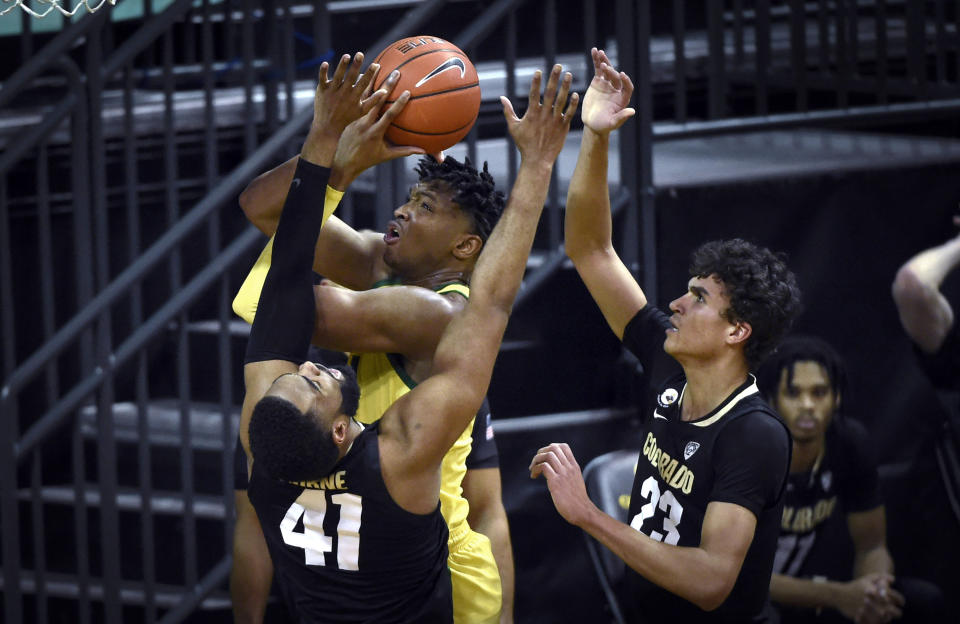 Oregon forward Chandler Lawson is fouled by Colorado forward Jeriah Horne (41) as he drives the lane past Colorado forward Tristan da Silva (23) during the first half of an NCAA college basketball game Thursday, Feb. 18, 2021, in Eugene, Ore. (AP Photo/Andy Nelson)