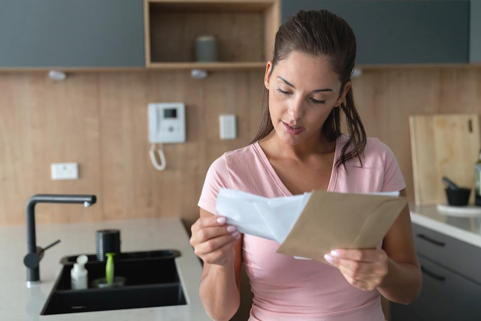 Portrait of a beautiful woman at home checking her mail in the kitchen holding envelopes - lifestyle concepts