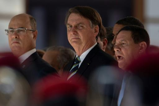Brazilian President Jair Bolsonaro (C), seen here at a ceremony marking the 130th anniversary of the Rio de Janeiro Military School (CMRJ), was the target of protests over deep budget cuts in public education