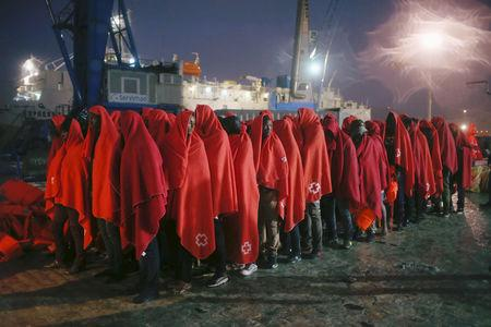 FILE PHOTO: Migrants stand under the rain after disembarking from a rescue boat at the port of Malaga
