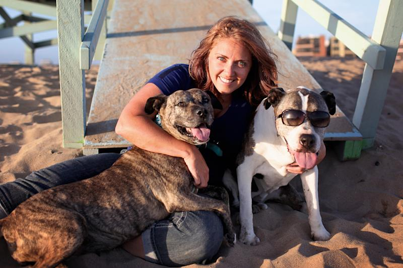 """This June 21, 2013 photo courtesy of Lori Fusaro shows photographer Lori Fusaro hugging her two dogs: Gabby, 10, left, and Sunny, 17, at Playa del Rey in Los Angeles. Fusaro is is working on """"Silver Hearts,"""" a photo book of old dogs. She plans to turn proceeds over to rescues that save old dogs and also hopes the book will encourage others to adopt old dogs. (AP Photo/Lori Fusaro)"""