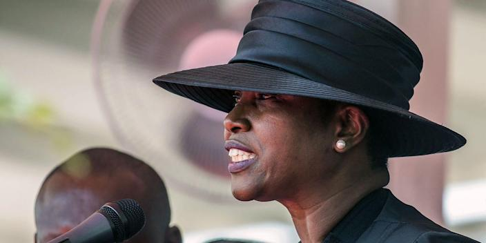 Martine Moïse, wearing a black hat, speaks at a microphone