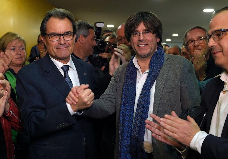 Catalan regional caretaker president Artur Mas (L) shakes hands with current mayor of Gerona, Carles Puigdemont (R) who will be the candidate for the Catalan regional presidency after Mas announced that he will not seek new term on January 9, 2016 (AFP Photo/Lluis Gene)