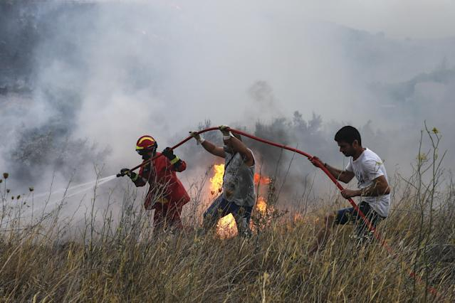 <p>Firefighters and volunteers try to extinguish the fire broke out at forested land in Penteli town of Athens, Greece on July 23, 2018. (Photo: Ayhan Mehmet/Anadolu Agency/Getty Images) </p>