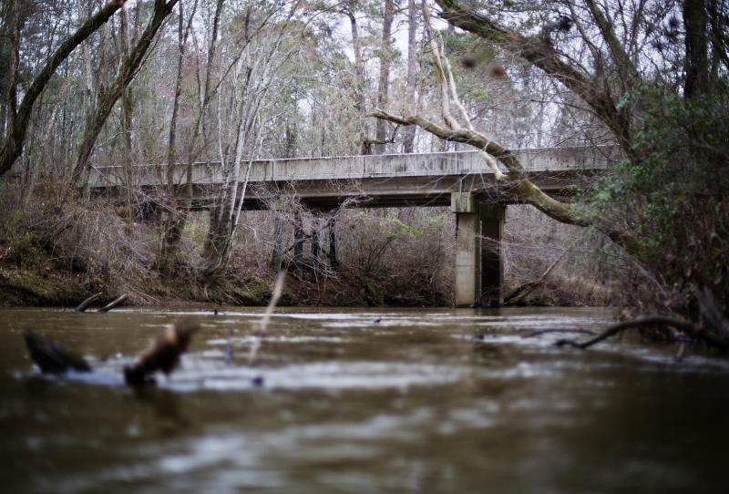 FILE- This Feb. 22, 2018, file photo shows a bridge that spans the Apalachee River at Moore's Ford Road where in 1946 two young black couples were stopped by a white mob who dragged them to the riverbank and shot them multiple times in Monroe, Ga. The gruesome lynching is prompting a U.S. court to consider whether federal judges can order grand jury records unsealed in old cases with historical significance. (AP Photo/David Goldman, File)