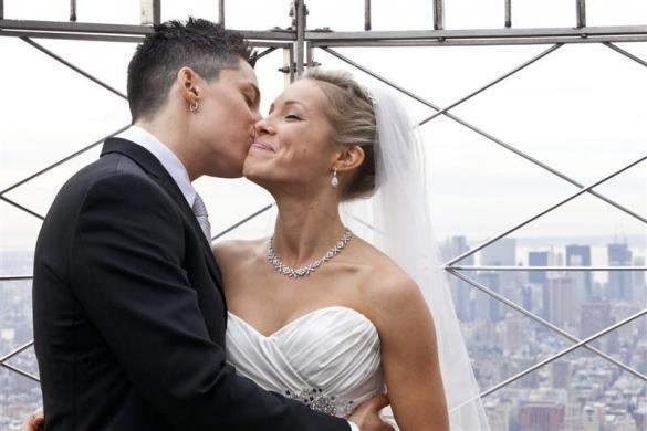 "Lela McArthur (R) and Stephanie Figarelle, both from Anchorage, AK, kiss on the observation desk of the Empire State Building after being married on the 61st floor in New York, February 14, 2012. Lucky couples have been married each year on Valentine Day's on the top of the Empire State Building for nearly two decades but this year for the first time two same sex couples said ""I do"" at the iconic New York landmark. The sky-high nuptials followed the legalization of gay marriage in June when Democratic Gov. Andrew Cuomo signed the law making New York the sixth, and most populous U.S. state, to approve gays and lesbians to wed."