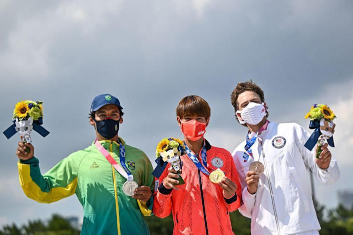 """Gold medallist Japan's Yuto Horigome (C), silver medallist Brazil's Kelvin Hoefler (L) and bronze medallist Jagger Eaton of the US pose on the podium at the end of the men's street prelims during the Tokyo 2020 Olympic Games at Ariake Sports Park Skateboarding in Tokyo on July 25, 2021.<span class=""""copyright"""">Jeff Pachoud–AFP/Getty Images</span>"""