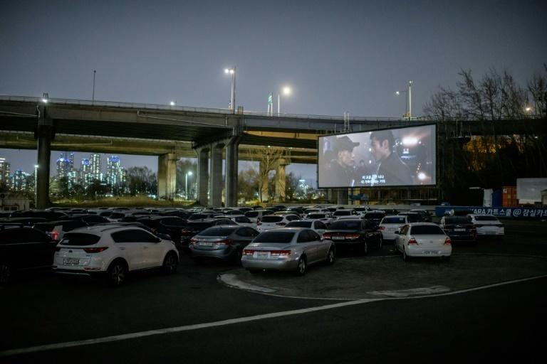 People can park their cars in front of a large outdoor screen