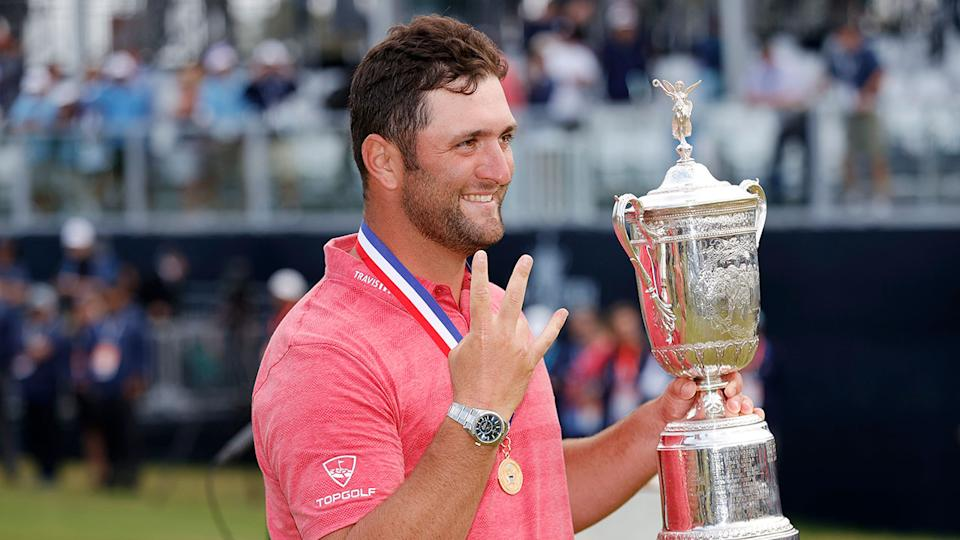 Pictured here, Jon Rahm holds the US Open trophy aloft.