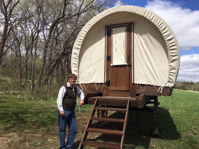 In this April, 11, 2019 photo, Dennis Steinman stands by the back door of one of his custom-built covered wagons outside his home in rural Douglas County, Kansas. Dennis and Donna Steinman have built the first of what they hope will be many 26-by-10-foot canvas-covered wagons. Their PlainsCraft Conestoga Wagons are more like the Winnebago of covered wagons; they're intended for those drawn to glamorous camping, or glamping. (Kathy Hanks/Lawrence Journal-World)