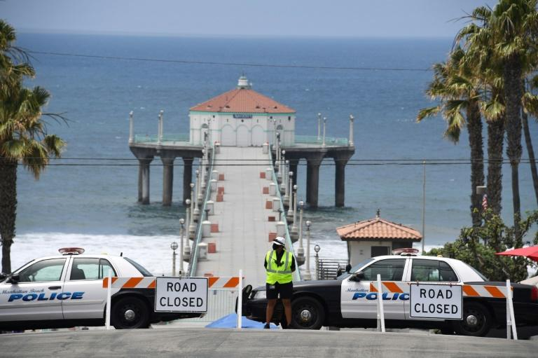 Police cars block the entrance to the pier in Manhattan Beach, California, on July 4, 2020, where beaches -- usually packed for Independence Day -- are closed due to a spike in COVID-19