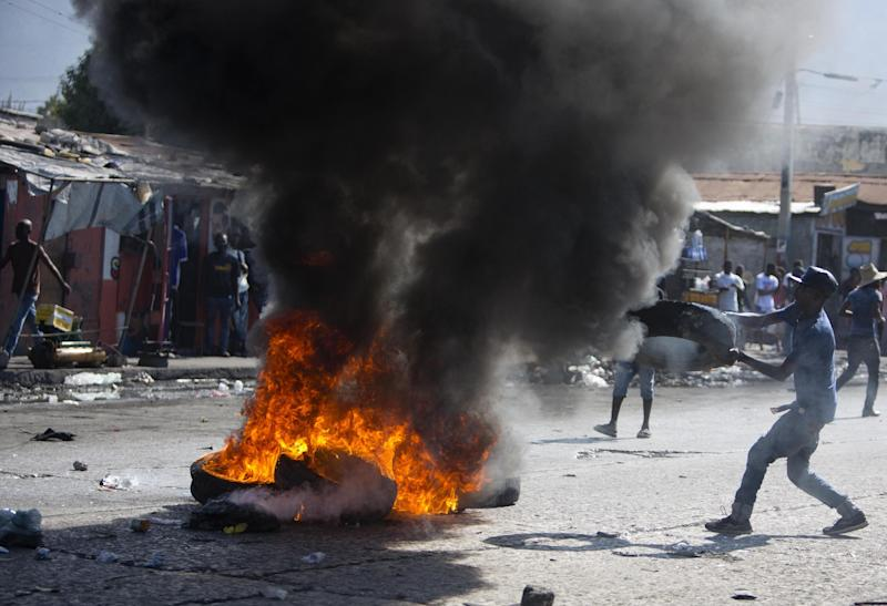 A supporter of presidential candidate Maryse Narcisse burns tires to protest the final election results in Port-au-Prince, Haiti, Tuesday, Jan. 3, 2017. An electoral tribunal certified the presidential election victory of first-time candidate Jovenel Moise. (AP Photo/Dieu Nalio Chery)