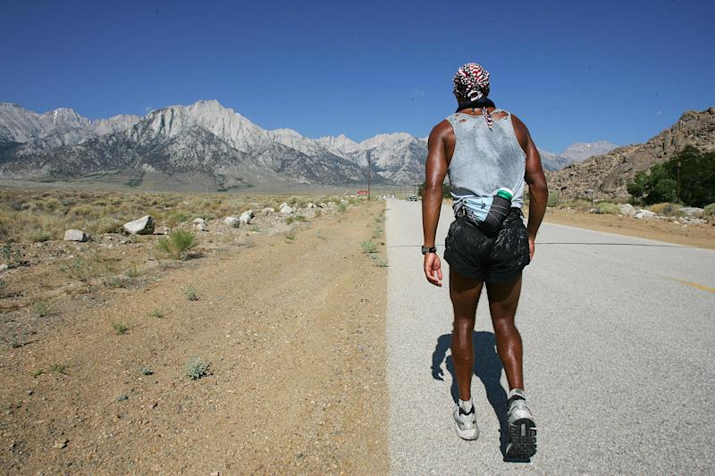 Lone Pine, UNITED STATES: Competitor David Goggins, 31, a US Navy Seal, faces Mt Whitney and the last 13 miles (21kms) of the 135-mile Kiehl Badwater Ultramarathon, 25 July, 2006, in Lone Pine, California. This foot race covers 135 miles (217kms) non-stop from Badwater, the lowest elevation in the Western Hemisphere at 282 feet (85.5 meters) below sea level, to Mt. Whitney Portals at 8,360 feet (2,533 meters) above sea level. Temperature in Death Valley hit 126F (52C) and three mountain ranges are crossed, making this one of the most demanding and extremem running races in the world. AFP PHOTO/ROBYN BECK (Photo credit should read ROBYN BECK/AFP via Getty Images)
