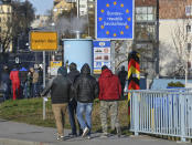 Polish commuters cross the border to enter Germany at the Stadtbruecke border crossing between Germany and Poland in Frankfurt an der Oder, Germany, Monday, March, 22, 2021. Poland is being classified as a 'high risk' COVID-19 area by German authorities and people crossing into Germany from Poland must provide a negative coronavirus test. (Patrick Pleul/dpa via AP)