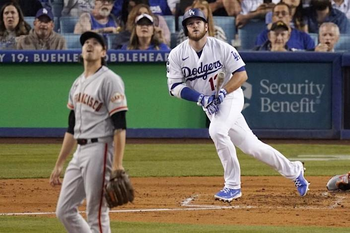Los Angeles Dodgers' Max Muncy, right, runs to first as he hits a solo home run while San Francisco Giants.
