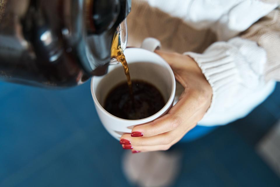 Close-up of a woman pouring herself hot filter coffee to a mug while staying at home.