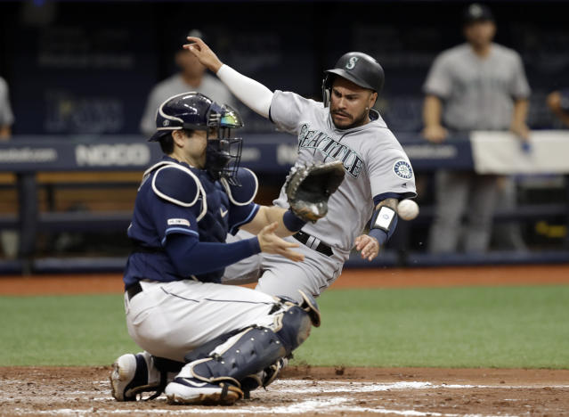 Seattle Mariners' Omar Narvaez, right, scores ahead of the throw to Tampa Bay Rays catcher Travis d'Arnaud on a two-run single by Tim Lopes during the fourth inning of a baseball game Wednesday, Aug. 21, 2019, in St. Petersburg, Fla. (AP Photo/Chris O'Meara)