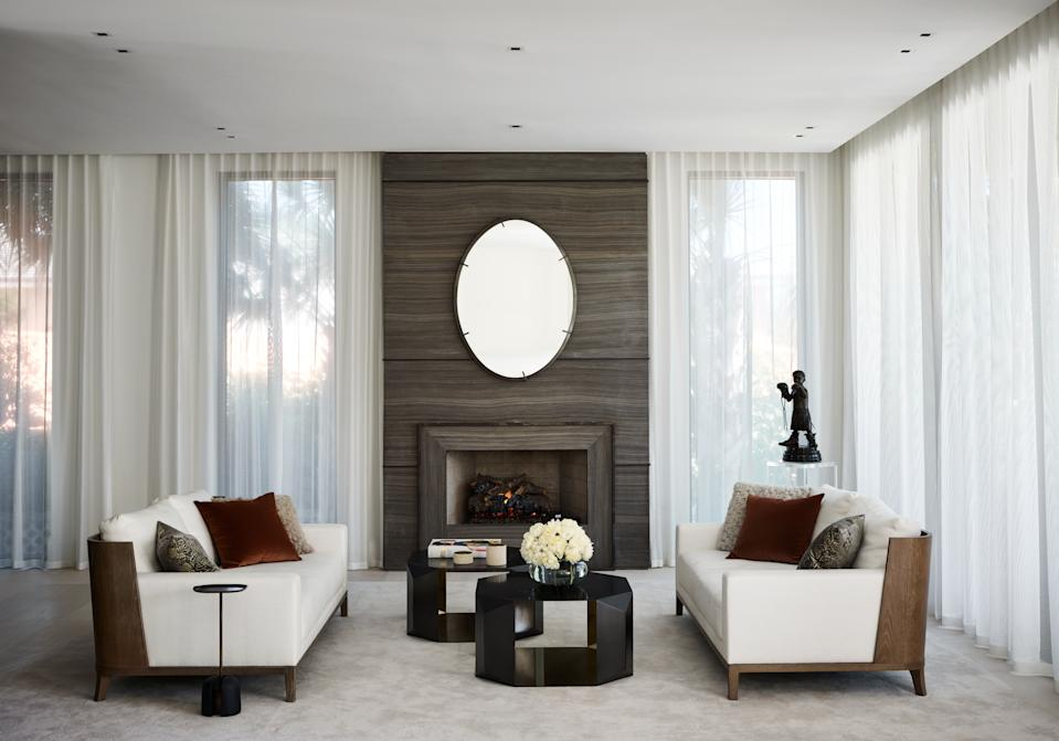 """<div class=""""caption""""> Joyner's family room is both sleek and cozy. The fireplace area is constructed of open-pore onitis marble with bronze inserts and was custom designed by Wecselman Design. The love seats are by <a href=""""https://www.liaigre.com/en/"""" rel=""""nofollow noopener"""" target=""""_blank"""" data-ylk=""""slk:Liaigre"""" class=""""link rapid-noclick-resp"""">Liaigre</a>, the coffee table is from Donghia, and the rug was another custom design, this one from Tai Ping. </div>"""