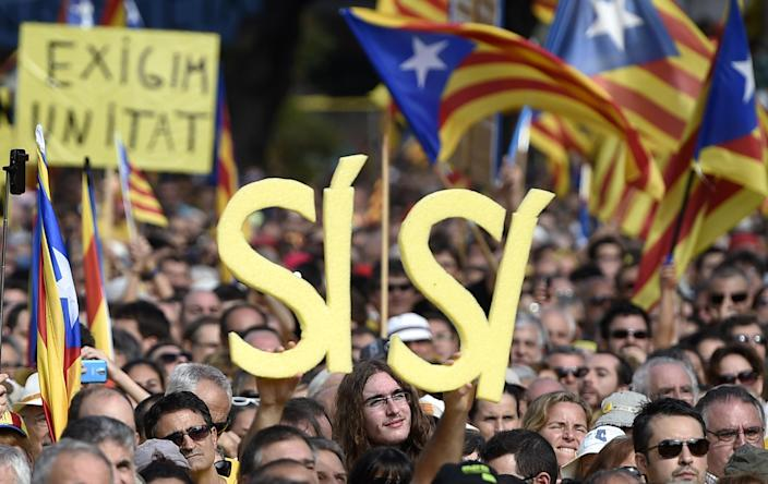 """Pro-independence Catalans hold signs reading """"Yes-Yes"""" in support of the independence referendum planned for November 9 in Barcelona, on October 19, 2014 (AFP Photo/Lluis Gene)"""