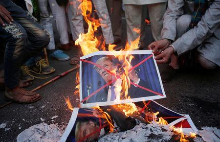 Protestors burn posters of U.S. President Donald Trump during a protest, organised by various religious organisations, against the U.S. decision to recognise Jerusalem as the capital of Israel, in New Delhi, India, December 17, 2017. REUTERS/Adnan Abidi