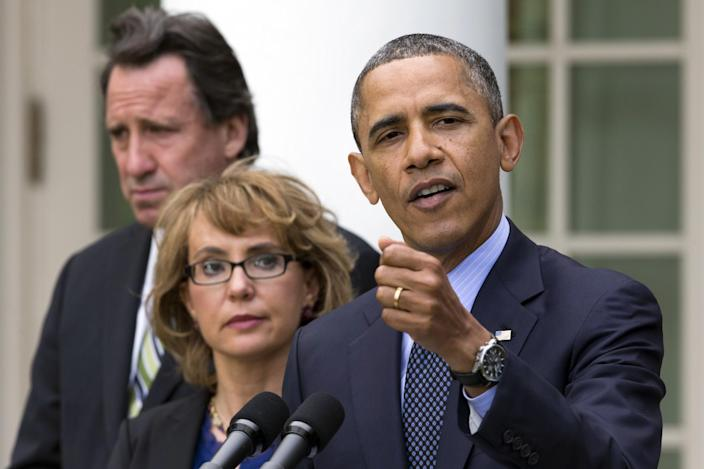 Neil Heslin, father of six-year-old Newtown victim Jesse Lewis, left, and former Rep. Gabby Giffords, D-Ariz., stands by President Barack Obama as he gestures while speaking during a news conference in the Rose Garden of the White House, in Washington, on Wednesday, April 17, 2013, about measures to reduce gun violence. (AP Photo/Jacquelyn Martin)