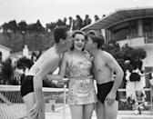 <p>Judy is kissed by fellow teen actors Jackie Cooper and Mickey Rooney at a birthday party hosted at studio head Louis B. Mayer's house. </p>