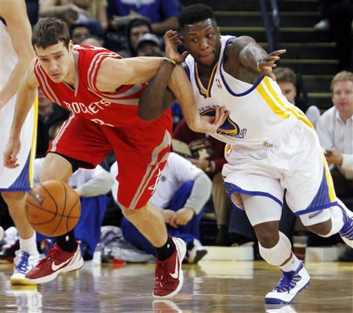 Houston Rockets' Goran Dragic, left and Golden State Warriors' Nate Robinson chase a loose ball during the first half of an NBA basketball game, Sunday, Feb. 12, 2012, in Oakland, Calif. The Warriors won 106-97. (AP Photo/George Nikitin)